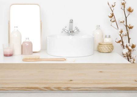 Wooden table top for product display and blurred bathroom