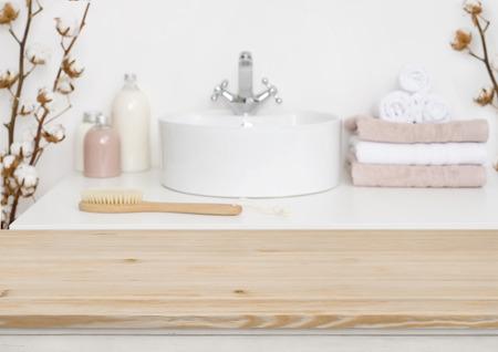 Piano del tavolo in legno e interni del bagno sfocati