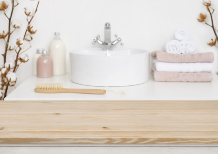 Wooden table top and blur bathroom interior Imagens