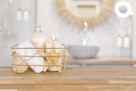 Basket with spa products on wood over blurred bathroom interior