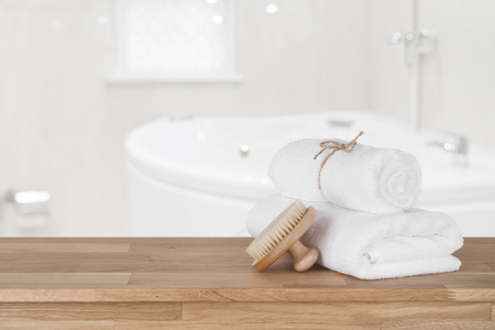 White spa towels on wooden table over defocused bathroom background Banco de Imagens