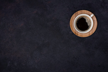 Coffee cup top view over the dark abstract surface background Banco de Imagens