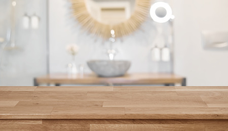 Wooden table top in front of blurred bathroom interior background Banco de Imagens