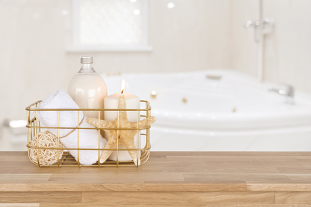 Spa products in basket on wood table over blurred bathtub