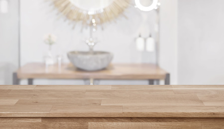 Wooden table in front of blurred bathroom sink interior background Banco de Imagens