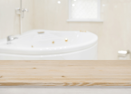 Wooden table for product display over defocused bathtub background Banco de Imagens