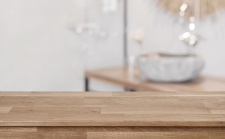 Defocused bathroom interior background with wooden table top in front