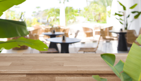 Defocused tropical summer cafe background in front of wooden tabletop Banco de Imagens