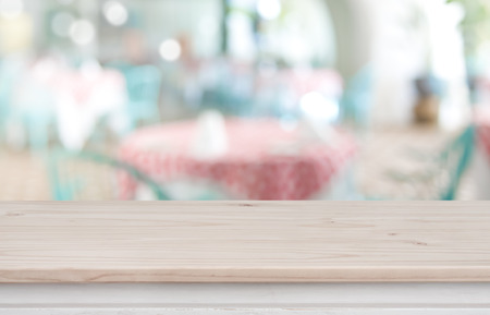 Defocused background of restaurant with wooden table top in front