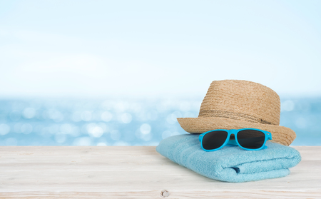 Beach towel, sunglasses and hat on wood over blurred seascape Banco de Imagens
