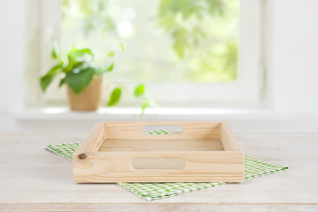 Empty wooden tray on table over blurred summer window background