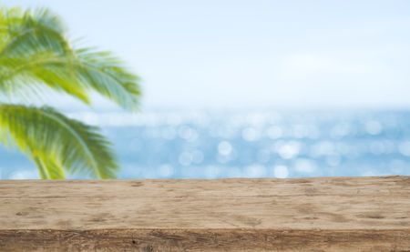 Defocused sea background with wooden table foreground for product display