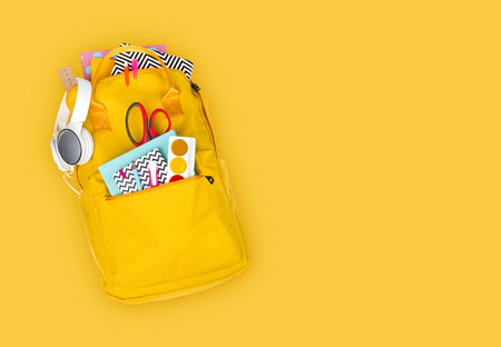 Backpack with school supplies and accessories isolated on yellow