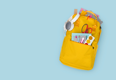 Backpack with school supplies, top view. Back to school concept