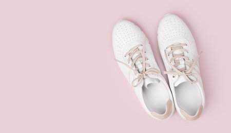White leather sneakers with laces isolated on pink