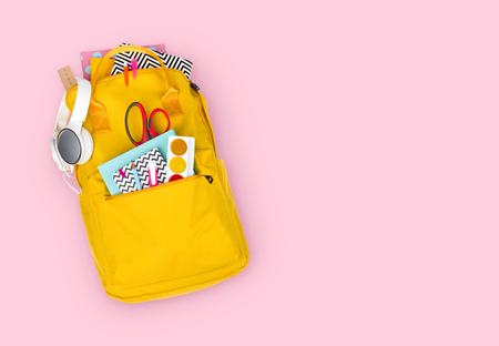 Yellow backpack with school supplies isolated on pink