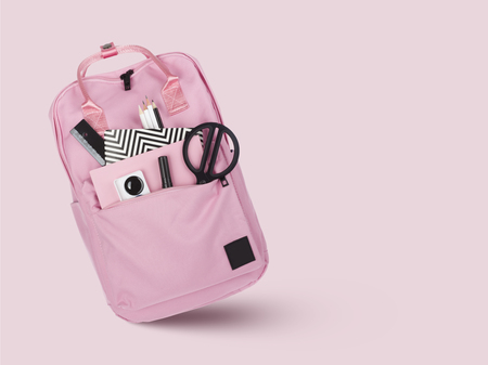 School backpack with various stationery tools isolated on pink Banco de Imagens