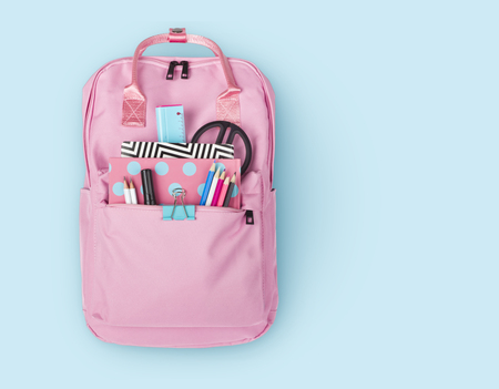 Children backpack with various school stationery isolated on blue