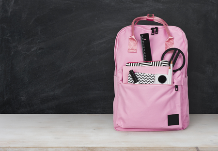 Educational concept. Backpack with school supplies on table before blackboard Banco de Imagens
