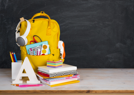 Back to school concept. Educational supplies on table before blackboard Stockfoto