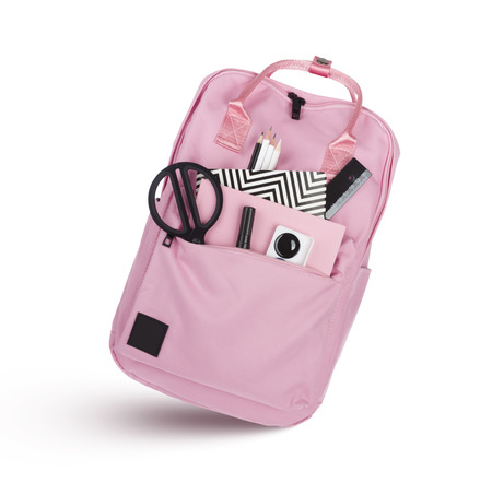 Pink school backpack with educational supplies isolated on white