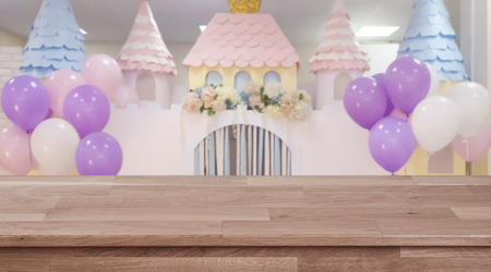 Empty wooden table with blurred wedding or birthday party