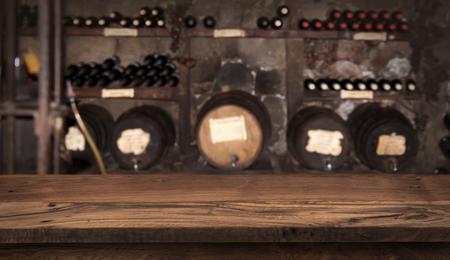 Wooden table on blurry  of wine barrels and bottles Banco de Imagens
