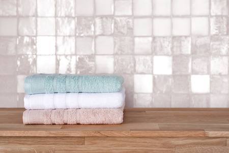 Bath towel pile on wooden surface before ceramic tile wall