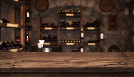 Defocused dark wine cellar  with wooden table in front