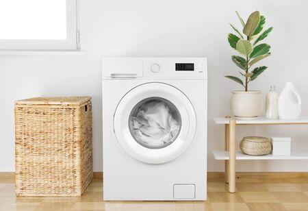 Washing machine with clothes in modern bathroom interior