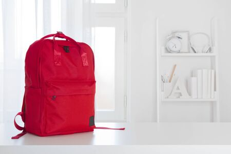 Red school backpack on table in children room interior