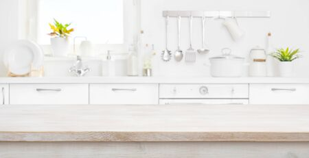 Defocused kitchen room and window with wood table in front Banco de Imagens - 125686719