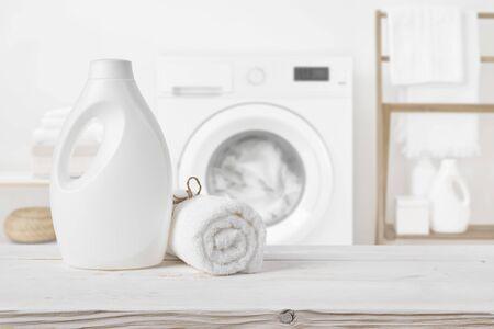 Plain detergent bottle on wood over defocused laundry room interior Banco de Imagens