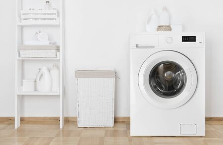 Interior of home laundry room with washing machine near wall Banco de Imagens - 125686828