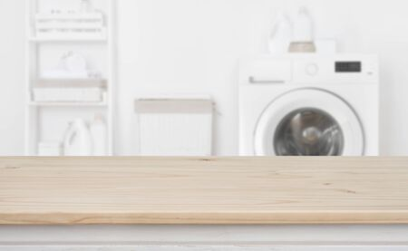 Wooden table in front of defocused washing machine and laundry Banco de Imagens - 125686826