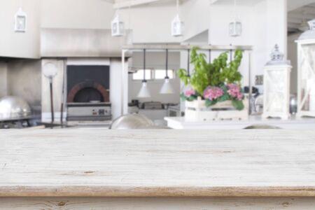 Drewniany blat na niewyraźnej nowoczesnej kuchni restauracyjnej