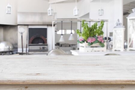 Wooden table top on blurred modern restaurant kitchen room