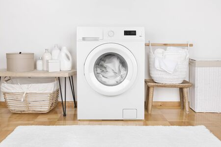 Domestic room interior with modern washing machine and laundry baskets