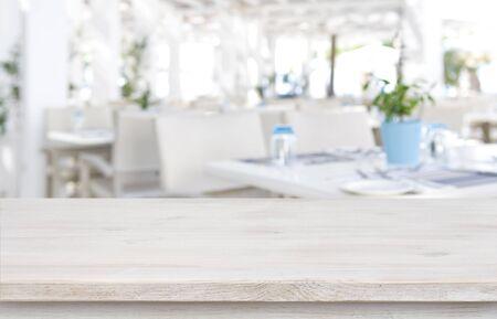 Defocused resort restaurant  with wooden table top in front Banco de Imagens