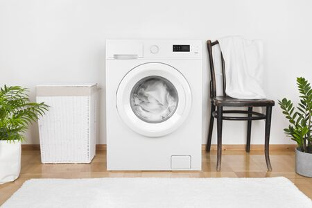 Interior of laundry room with washing machine and laundry basket