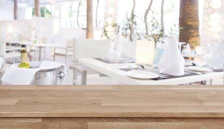 Wooden table top on defocused restaurant  with set tables Banco de Imagens