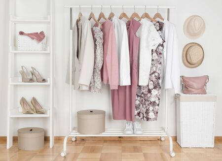 Collection of female clothes hanging on rack in dressing room Banco de Imagens - 129360515