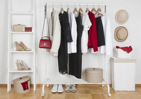 Modern wardrobe interior with different female clothes, hats and shoes Banco de Imagens