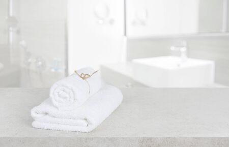 White towels on table in defocused bathroom with copy space