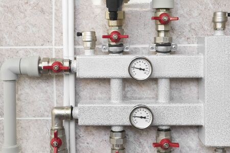 Close-up of house heating collector with pipes, manometers and valves Banco de Imagens - 130911460