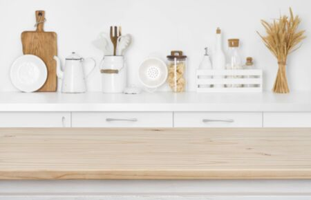 Blurred kitchen counter with utensils and ingredients over wooden table