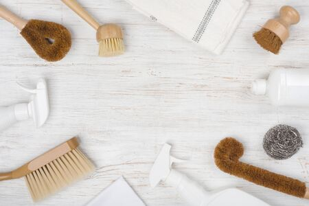 Eco natural cleaning brushes, cloth and detergent on wooden background