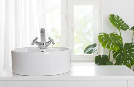 Hygienic wash basin with chrome faucet on bathroom window