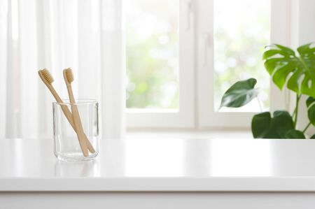 Two wooden toothbrushes in glass on blurred window background