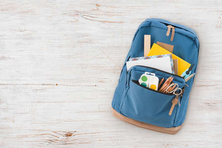 Backpack with different school supplies isolated on vintage wooden background Standard-Bild